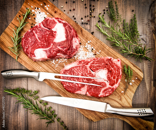 Staande foto Vlees Raw fresh meat Ribeye Steak with herbs and spices. Retro style