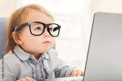 Fotomural Intelligent toddler girl wearing big glasses while using her laptop