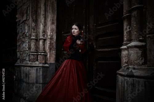 Mysterious woman in red Victorian dress with a candle