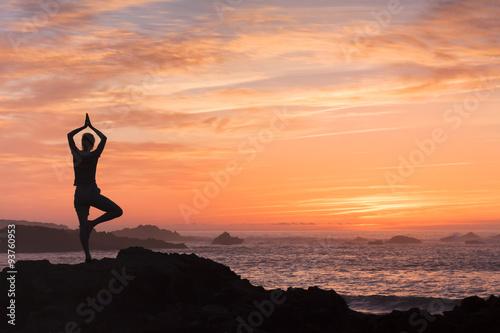 Fotografia  Woman fighting anxiety with yoga near the sea
