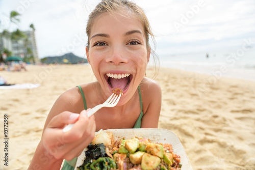 Funny woman eating salad healthy meal on beach