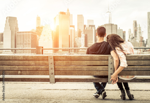 Staande foto New York couple relaxing on New york bench in front of the skyline at sun
