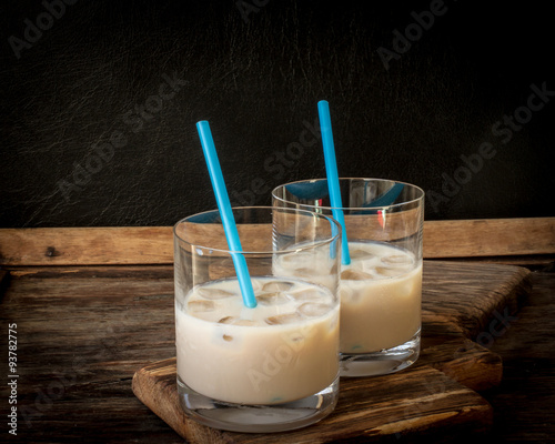 Photo  Irish cream liqueur in a glass with ice.