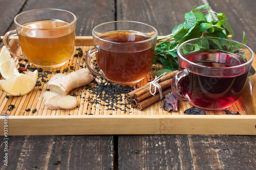 Staande foto Thee Three cups of tea with lemon, ginger, cinnamon and mint