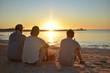 Jungs mit Bier bei Sonnenuntergang am Meer