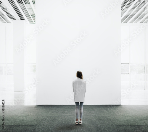 Young woman walking through a gallery and looking at the canvas Wallpaper Mural