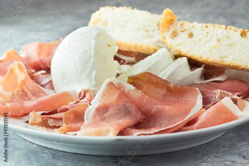 Staande foto Buffel Prosciutto crudo e mozzarella di bufala, con pane nel piatto da portata, antipasto bufala campana