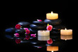 Spa stones and candles on dark background