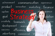 Businesswoman writing business strategy concept. Blue background.
