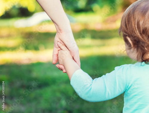 Fotografering  Toddler girl holding hands with her mother