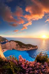 Panel Szklany Optyczne powiększenie Navagio beach with shipwreck and flowers against sunset, Zakynthos island, Greece