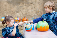 Two Little Kids Painting With Colors On Pumpkin
