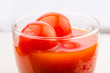 macro photo of tomato juice and cherry tomatoes in glass on gray background