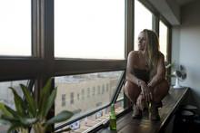 Woman Crouching On A Window Sill