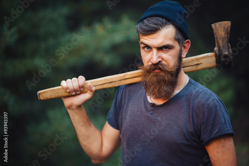 Fotografie, Obraz  Brutal brunette bearded man in warm hat with a hatchet in the woods on a backgro