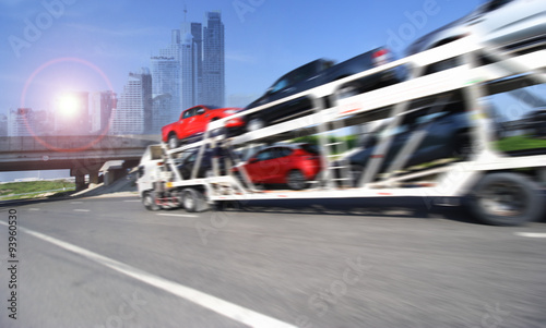 Photo  The trailer transports cars on highway with big city background