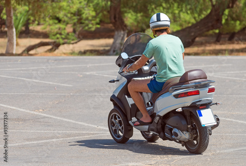 Man on  three-wheel scooter. View from the back.