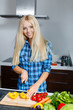Beautiful woman preparing a salad in the kitchen