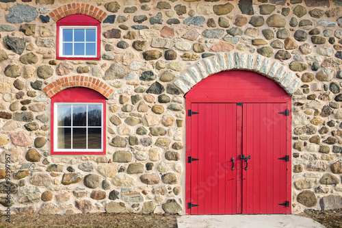 fototapeta na lodówkę Bright Red Arched Door and Windows in a Stone Wall