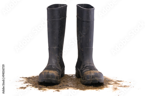 Cuadros en Lienzo  Muddy rubber boots front view isolated on white background