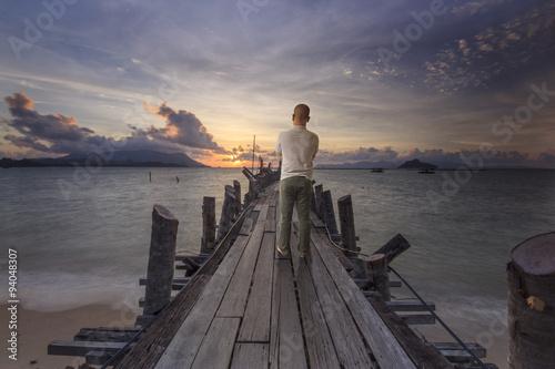 Cadres-photo bureau Lavende Man on the pier to look far into the sun