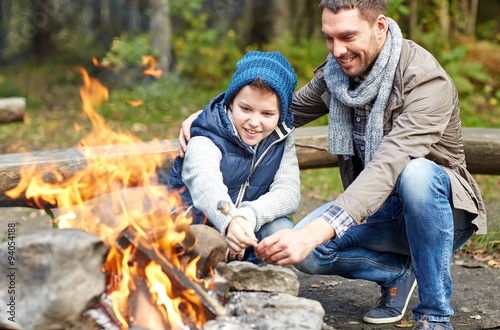 Obraz father and son roasting marshmallow over campfire - fototapety do salonu