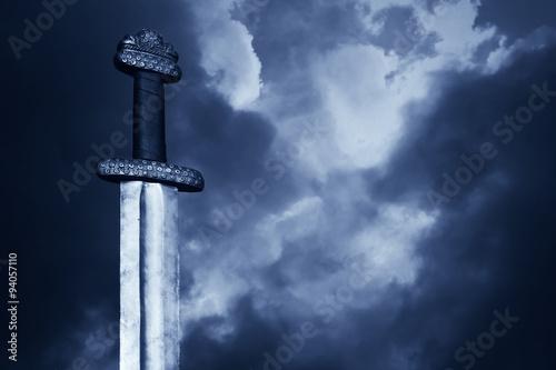 Medieval viking sword against a dramatic sky Wallpaper Mural