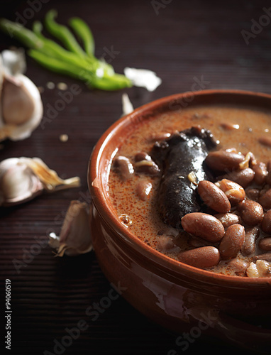 Spanish fabada with Black pudding in an earthenware dish on rustic background