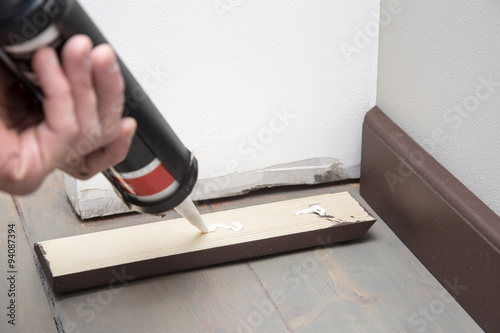 home improvement, pushing glue on the wooden baseboard Wallpaper Mural