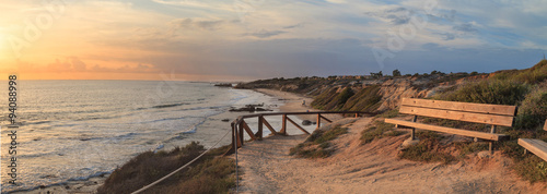 Cuadros en Lienzo Bench along an outlook with a view at sunset of Crystal Cove Beach, Newport Beac