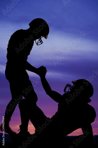 silhouette of one football player helping another up
