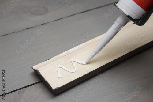 Obraz putting glue on a piece of wooden baseboard - fototapety do salonu