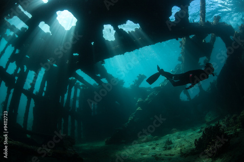 Fotomural Free Diver Swimming Through Shipwreck