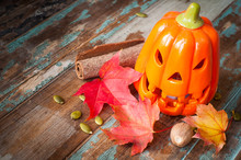 Ceramic Carved Halloween Pumpkin Jack O Lantern With Autumn Fall Leaves And Berries On A Rustic Wooden Table.