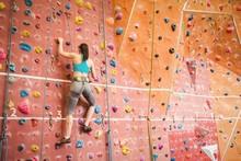 Woman Climbing Up Rock Wall