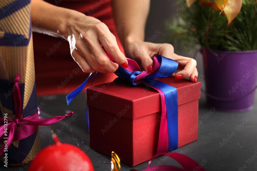 Fototapeta Pięknie zapakowany prezent. Kobieta pakuje prezenty, krok po kroku