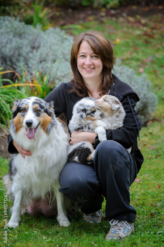 Stampa su Tela Dog breeder with Australian Shepherd adult female dog and her puppies in arms