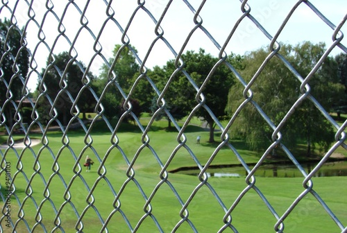 Fotografie, Obraz  Chan Link fence with golf course and golfer in background