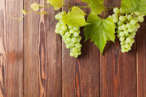 wiazka-biali-winogrona-z-liscmi-na-drewnie