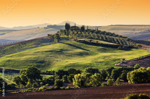 Fotografering  Tuscany landscape at sunrise. Tuscan farm house, green hills.