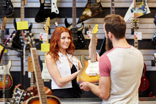 Spoed Foto op Canvas Muziekwinkel assistant showing customer guitar at music store