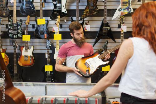 Spoed Foto op Canvas Muziekwinkel assistant showing customer guitar at music store