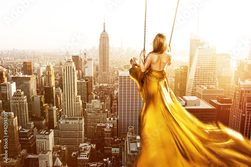 Fotografia  Woman on a swing above New York City