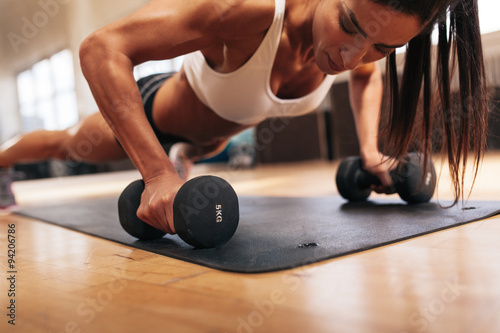 Poster  Muscular woman doing push-ups on dumbbells