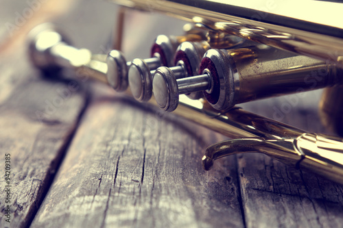 Cuadros en Lienzo Trumpet on an old wooden table. Vintage style.