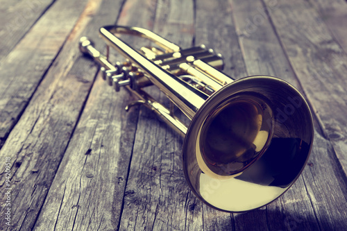 Fotografia Trumpet on an old wooden table. Vintage style.