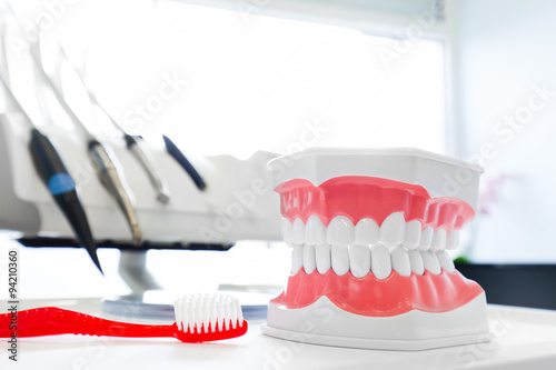 Clean teeth denture, dental jaw model and toothbrush in dentist's office плакат