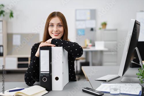 Fotografía  lächelnde frau im büro stützt sich auf aktenordner