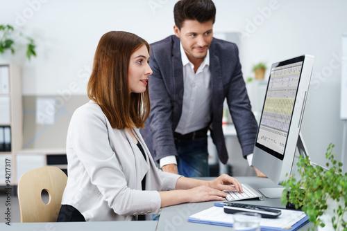 Fotografía  zwei mitarbeiter im büro schauen gemeinsam auf unternehmenszahlen