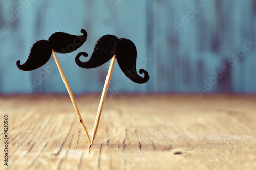 Photo  felt mustaches in sticks on a wooden surface